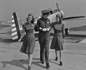 Photographie en noir et blanc d'un pilote avec 2 hôtesses de l'air.