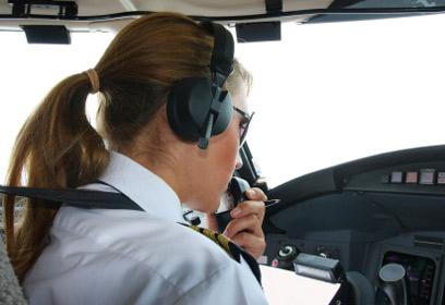 Photographie d'une jeune femme aux commandes d'un avion.