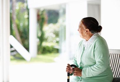 Photographie d'une personne âgée seule assise sur un banc.
