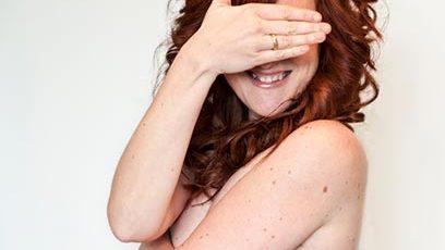 Photographie d'une femme nue se cachant le visage et les seins.