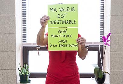 Femme tenant un papier où il est écrit « Ma valeur est inestimable »