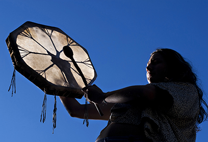Photographie d'un autochtone frappant sur un tambour