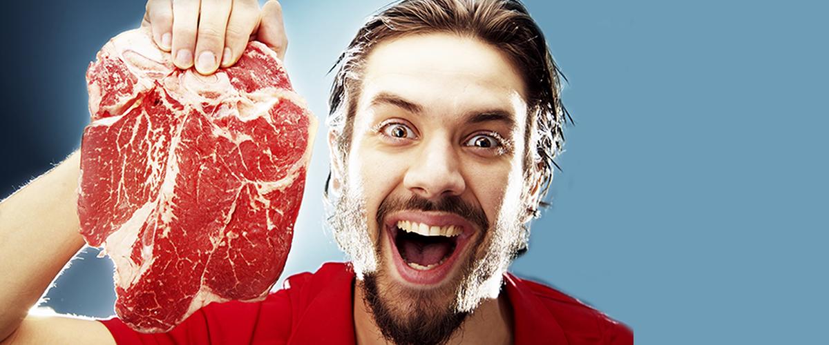 Photographie d'un homme tenant une tranche de steak dans la main.