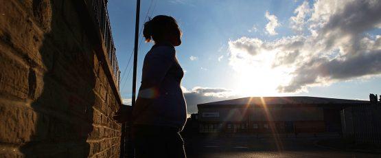 Photo d'une femme appuyée sur un mur regardant le soleil à l'horizon.