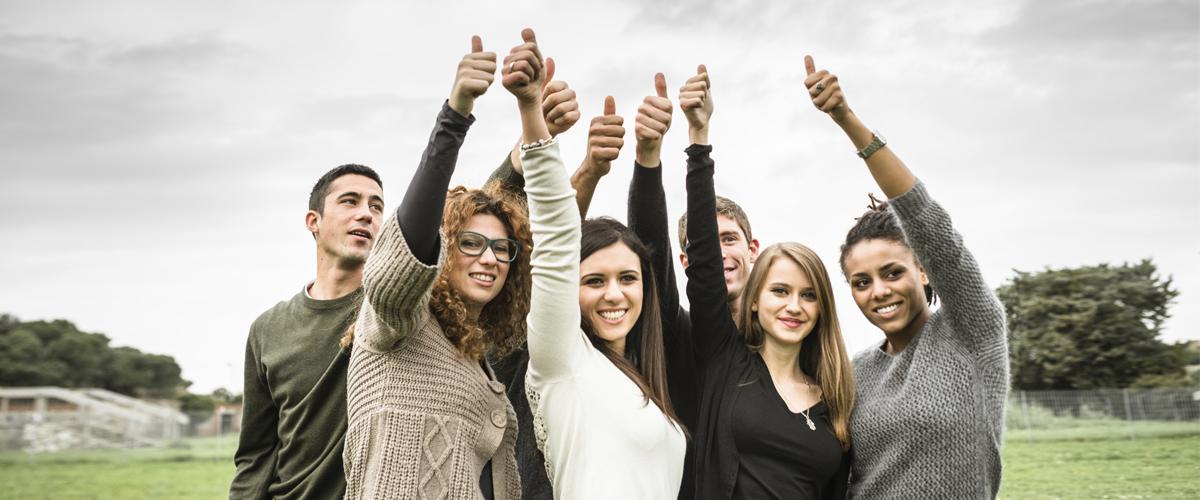 Photographie de plusieurs personnes levant un bras dans les airs.