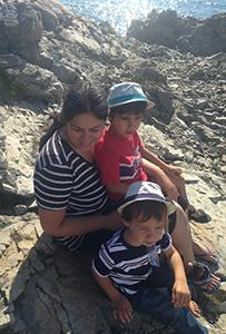 Camélia assise en bord de mer avec ses 2 enfants.