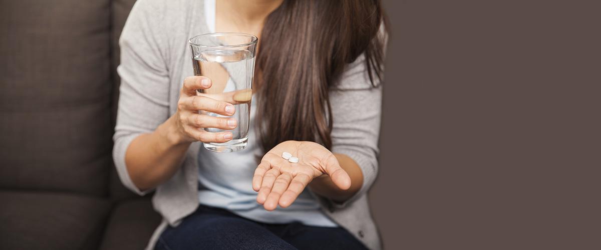 Jeune femme tenant 2 pilules abortives et un verre d'eau.