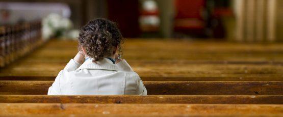 Une jeune femme de dos assise à l'église.