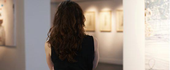 Photographie une jeune femme vue de dos, regardant une galerie.