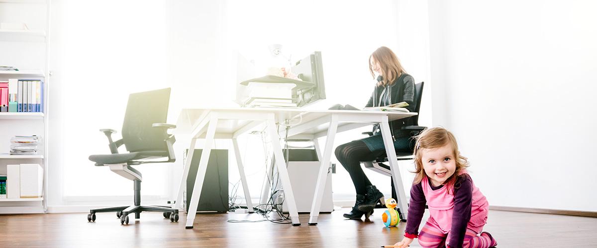 Jeune mère à l'ordinateur avec son enfant qui joue.