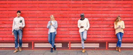 4 personnes appuyées en ligne sur un mur rouge.