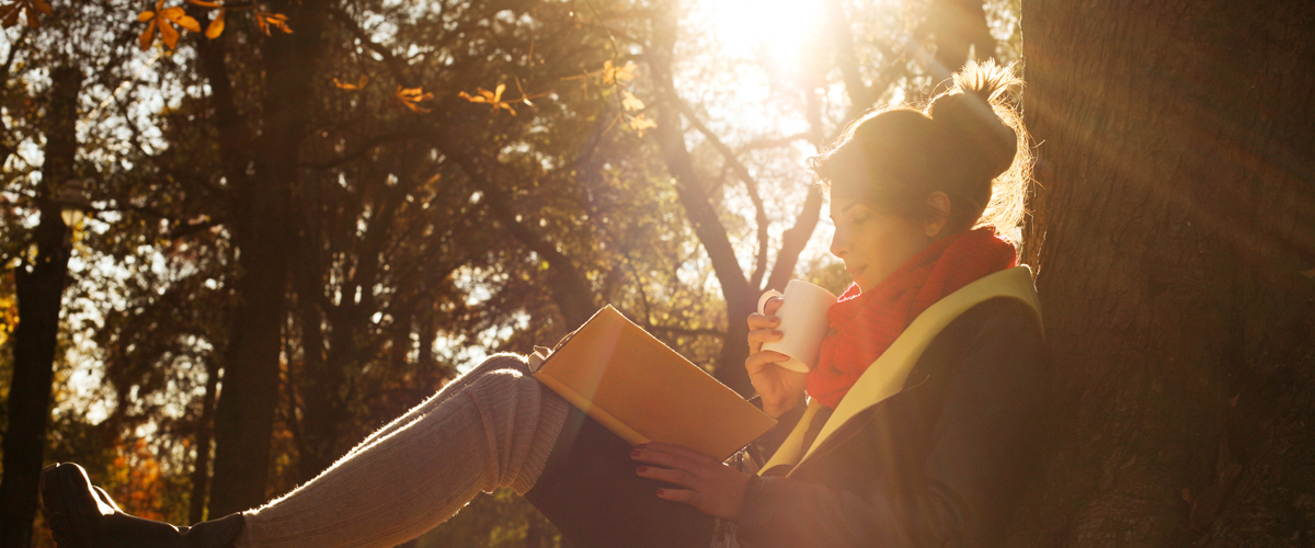 Photographie d'une femme lisant un livre dans la fotêt.