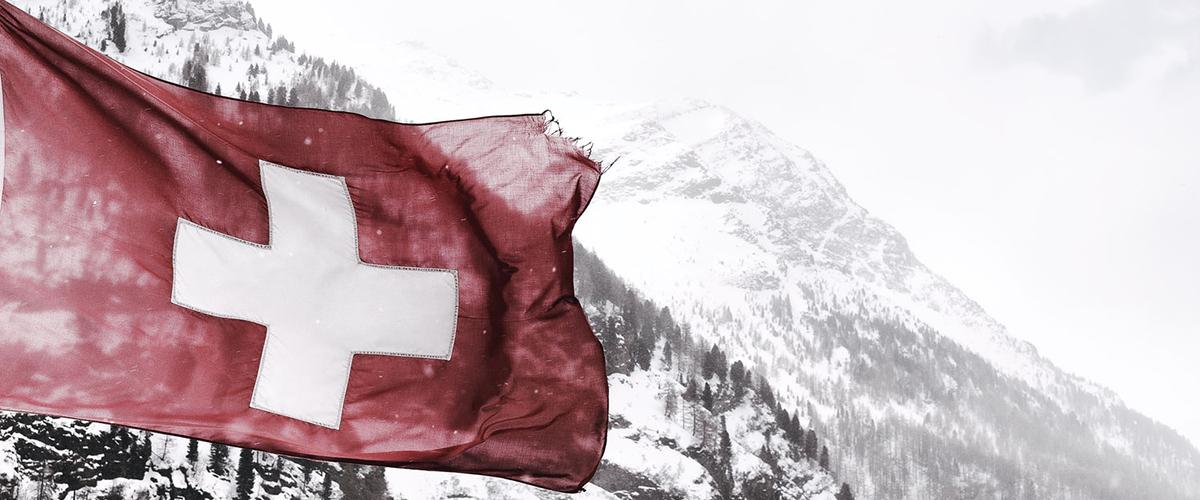 Drapeau de la Suisse flottant à la cime d'une montagne enneigée.